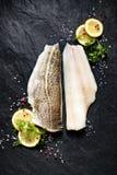Peixes frescos, faixa de bacalhau crua com adição de ervas e fatias do limão no fundo de pedra preto Fotos de Stock Royalty Free