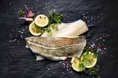 Peixes frescos, faixa de bacalhau crua com adição de ervas e fatias do limão no fundo de pedra preto Foto de Stock Royalty Free