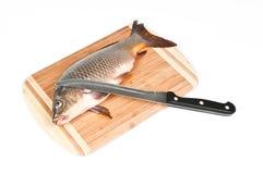 Peixes frescos na placa de corte com faca imagens de stock royalty free