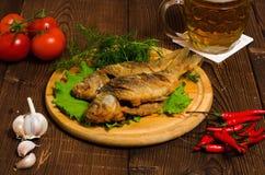 Peixes fritados com cerveja na tabela de madeira fotos de stock