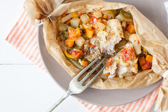Peixes fritados com os vegetais no pergaminho Imagens de Stock Royalty Free