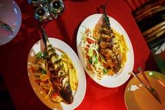 Peixes fritados com vegetais em um recipiente em uma toalha de mesa vermelha, fluxo bonito Culinária asiática fotografia de stock