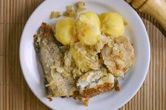 Peixes fritados e mentiras fervidas das batatas em uma placa em um guardanapo de bambu Close-up, foco seletivo imagem de stock