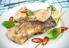 Peixes fritados na placa e na forquilha brancas, faca imagem de stock