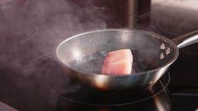 Peixes fritos, a faixa do atum na frigideira cozinhando no movimento lento video estoque