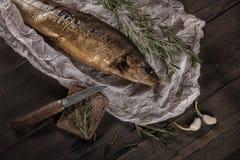 Peixes fumado com a faca do pão e do damasco na tabela de madeira Imagem de Stock