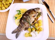 Peixes grelhados com batatas, molho e limão imagens de stock