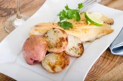 Peixes grelhados com batatas vermelhas Imagem de Stock Royalty Free