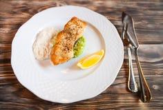 Peixes grelhados com fatia de limão e do sause branco no backg de madeira Fotos de Stock Royalty Free