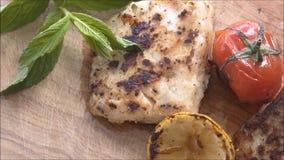 Peixes grelhados com os vegetais no fundo de madeira filme