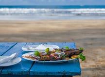 Peixes grelhados deliciosos na tabela azul Ondas de oceano no fundo Fotografia de Stock Royalty Free