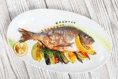 Peixes grelhados do dorado com vegetais e alecrins cozidos na placa no fim de madeira do fundo acima foto de stock royalty free