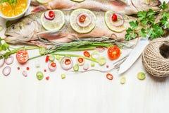 Peixes inteiros frescos com os ingredientes desbastados para o cozimento saboroso imagens de stock royalty free