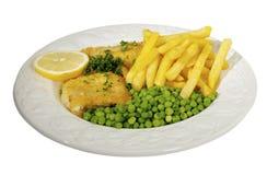 Peixes, microplaquetas e ervilhas decorados com limão e paridades Fotos de Stock Royalty Free