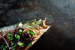Peixes Roasted decorados com as cebolas vermelhas e verdes imagem de stock royalty free