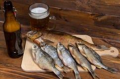 Peixes secos no fundo de madeira com cerveja Imagens de Stock