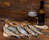 Peixes secos no fundo de madeira com cerveja Foto de Stock