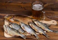 Peixes secos no fundo de madeira com cerveja Fotos de Stock