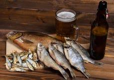 Peixes secos no fundo de madeira com cerveja Fotografia de Stock