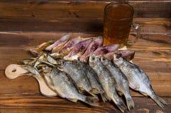 Peixes secos no fundo de madeira com cerveja Foto de Stock Royalty Free