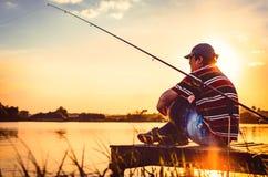 Peixes travados pescador Peixes caucasianos da captura do homem no lago Pescador na pesca do rio esporte dos homens do pescador d imagens de stock royalty free