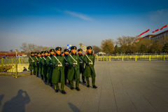 PEKÍN, CHINA - 29 DE ENERO DE 2017: Soldados chinos del ejército que marchan en las capas uniformes cuadradas del verde de Tianme Fotos de archivo