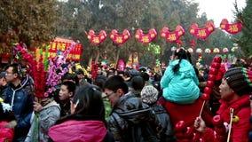 Pekín, China 6 de febrero de 2014: Porciones de visitantes que sostienen los juguetes en el templo de Ditan justos durante festiv almacen de video