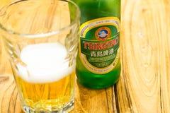 PEKÍN, CHINA - 22 DE MAYO DE 2016: Bottel de la cerveza de Tsing Tao al lado de a Foto de archivo libre de regalías
