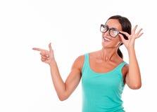 Peka brunettkvinnan med grön ärmlös tröja Arkivfoton
