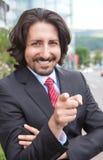 Peka den turkiska affärsmannen med dräkten som är främst av hans kontor Royaltyfria Bilder
