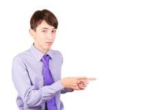 Peka din produkt Stående av den stiliga tonåriga pojken i skjorta och bandet som pekar utrymme och att le för kopia som isoleras  Royaltyfri Bild