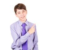 Peka din produkt Stående av den stiliga tonåriga pojken i skjorta och bandet som pekar utrymme och att le för kopia som isoleras  Royaltyfri Fotografi