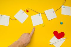 Peka fingret på ett stycke av papper, ställe för text, gul bakgrund arkivfoto