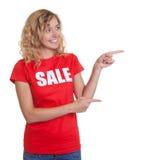 Peka kvinnan med blont hår i en försäljningsskjorta Arkivfoton