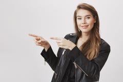 Peka på det stora stället Studioskott av den härliga moderna kvinnliga studenten, i lämnat att indikera för läderomslag med index royaltyfria bilder