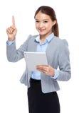 Pekar den digitala minnestavlan och fingret för affärskvinnahåll upp Royaltyfri Fotografi