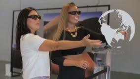 Pekar virtuell verklighetbegreppet, den futuristiska en hacker, två kvinnor med exponeringsglas av virtuell verklighet arkivfilmer