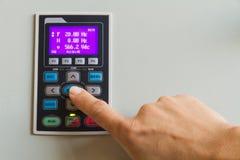 Pekfingerhandlaget skriver in på strömbrytaren på kontrollbordet Arkivfoto