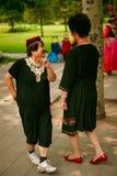 Pekin, Chiny 07 06 2018 Dwa szczęśliwych kobiet w jaskrawych sukniach tanczą w parku obraz royalty free