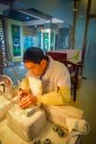 PEKIN, CHINY - 29 STYCZEŃ, 2017: Chabeta rzemieślnika obsiadanie biurkiem używać elektrycznego narzędziowego działanie z pełną ko Zdjęcie Stock