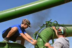 Young boy worker cranking blower pipe of a threshing machine. PEKIN, NORTH DAKOTA, September 2, 2018: Two unidentified workers move the thresher blower pipe with royalty free stock photography