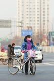 Peking-Bewohner mit Smogschutz Stockfotos
