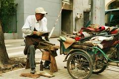 Peking, China - Juni 10, 2018: Het Chinese bejaarde herstelt schoenen op de straat van Peking stock foto's