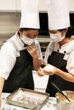 Peking China - 10 Juni, 2018: Twee chef-koks maken koekjesdeeg op een dienblad van het ijzerbaksel op royalty-vrije stock afbeelding