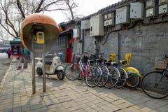 PEKING, CHINA - 12. MÄRZ 2016: Fahrräder, Roller und Autos herein Lizenzfreie Stockfotos