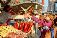PEKING, CHINA - 11. MÄRZ 2016: Lebensmittelverkäufer bietet sein Produkt an Stockbilder