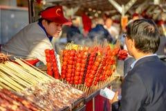 PEKING, CHINA - 11. MÄRZ 2016: Lebensmittelverkäufer bietet sein Produkt an Lizenzfreies Stockbild