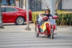 PEKING, CHINA - 12. MÄRZ 2016: Leute fahren durch Stockbild