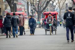 PEKING, CHINA - 12. MÄRZ 2016: Touristen in einer Rikscha in einer Hütte Lizenzfreies Stockbild