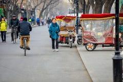 PEKING, CHINA - 12. MÄRZ 2016: Touristen in einer Rikscha in einer Hütte Stockbild